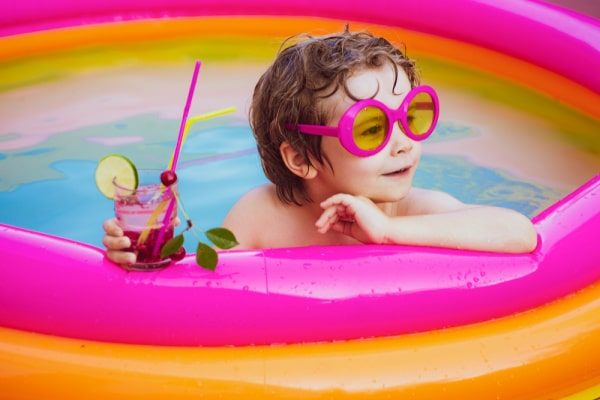 Beach Party Sleepover Fun child in a baby pool with funny pink sunglasses and a summer drink with colorful straws