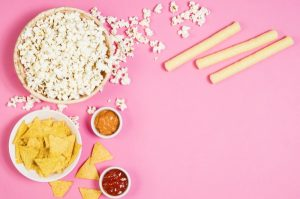 Best Sleepover Snacks List pink tabletop with sleepover food like popcorn, breadsticks, tortilla chips and salsas
