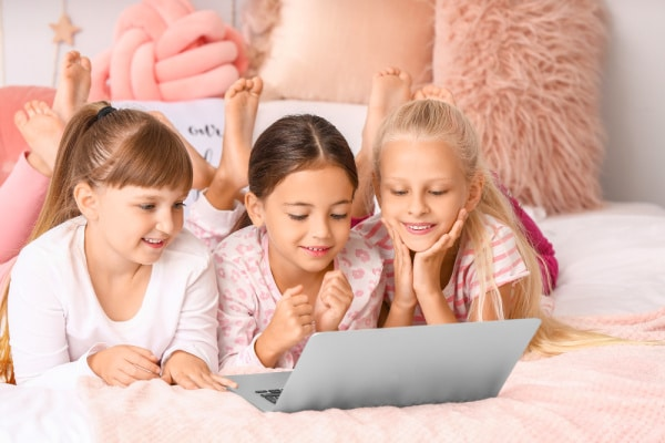 How To Host An Online Sleepover 3 girls in sleepover pajamas looking at a laptop