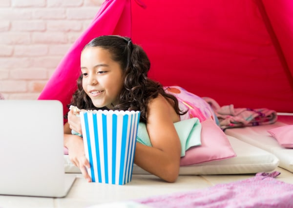 How to Have a Netflix Sleepover Party tween girl at sleepover looking at laptop and eating popcorn