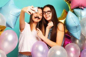 Senior Sleepover Ideas two senior girls posing with graduation balloons and photo props