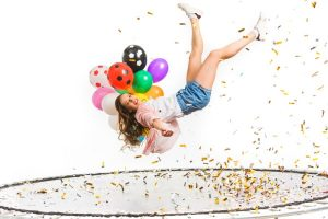 Trampoline Sleepover Ideas with teen girl holding balloons on trampoline and confetti flying around