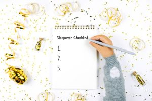 What To Bring To Sleepovers notebook with kid's hand making a sleepover checklist