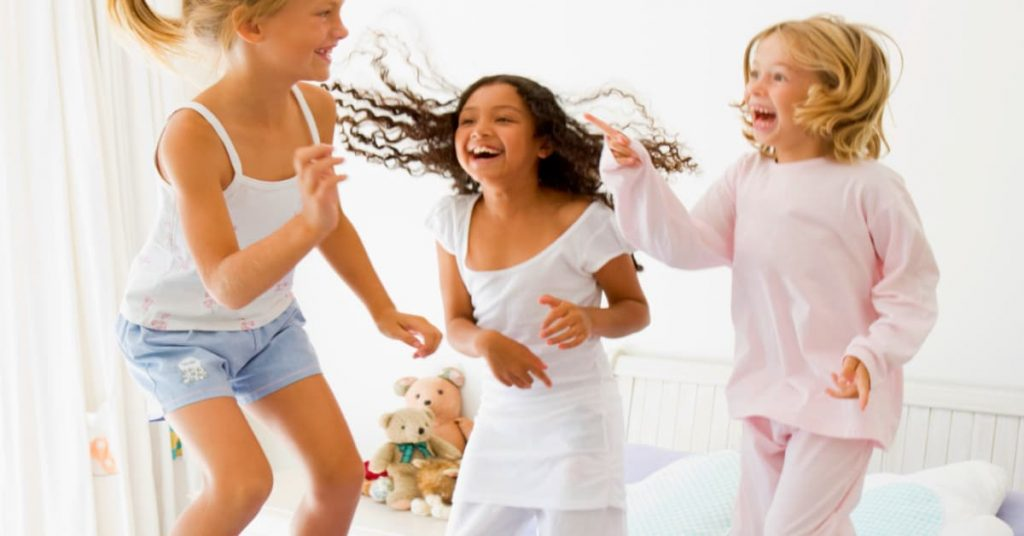 Best Girls Sleepover Ideas 3 girls laughing and jumping on a bed at a slumber party