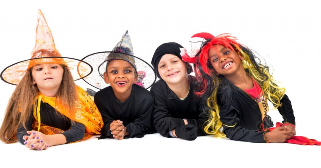 Halloween Birthday Sleepover Ideas four kids dressed in Halloween costumes lying on their stomachs and smiling into the camera