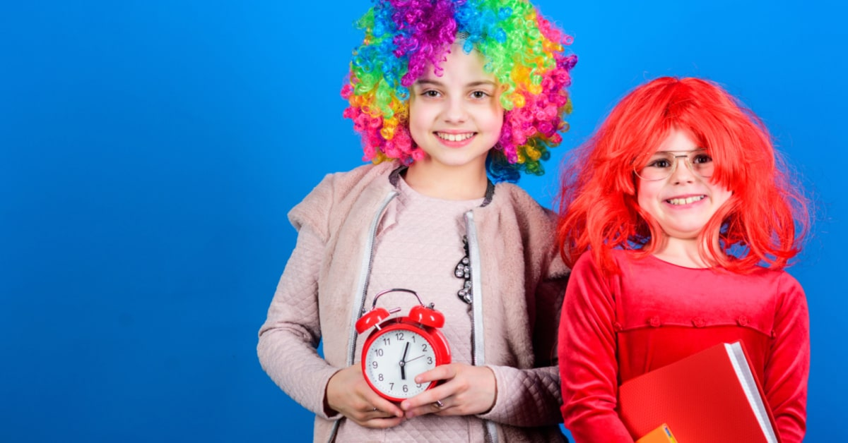 back to school sleepover with two young girls in crazy hair day wigs holding an alarm clock and school books
