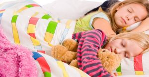 pros and cons of sleepover with two girls sleeping under colorful blanket