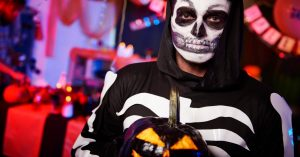 teen halloween party ideas with dressed up male teenager in skeleton costume with Halloween party decorations in background