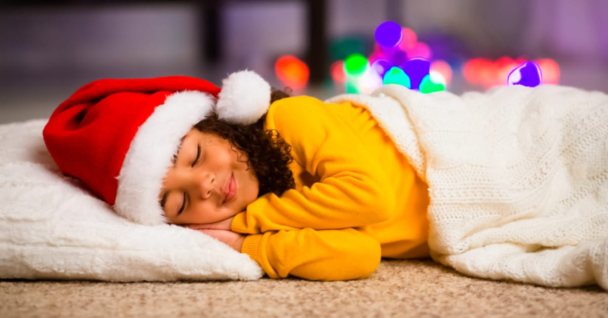 Christmas Eve sleepover ideas young african american girl in santa hat sleeping at a christmas eve sleepover party