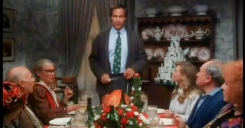 How To Have A National Lampoons Christmas Vacation Party Clark Griswold at head of Thanksgiving dinner table cutting dry turkey while guest look on